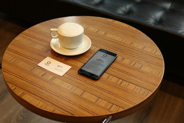 Smartphone et maquettes de cartes de visite psd sur table ronde à caffee