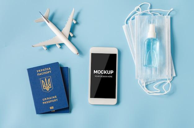 Smartphone avec modèle d'avion, passeports, masque facial et désinfectant