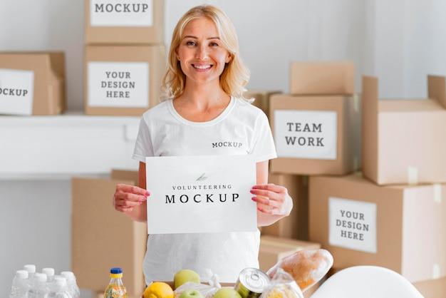 Smiley femme bénévole tenant du papier vierge à côté de la boîte de nourriture