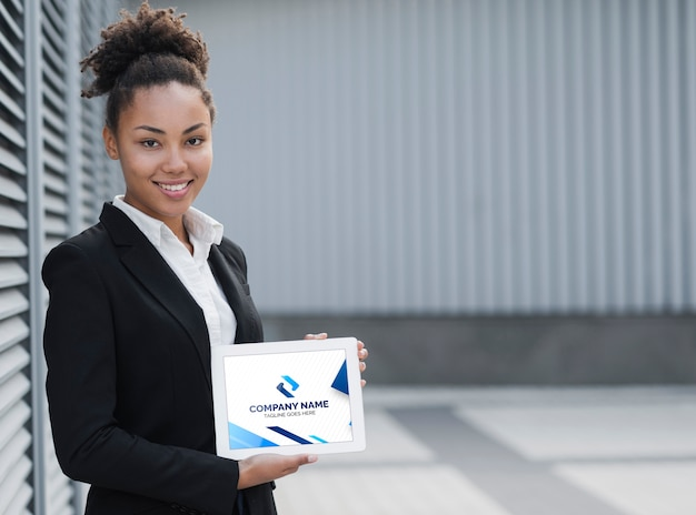 Sourire de femme d'affaires tenant une maquette de tablette