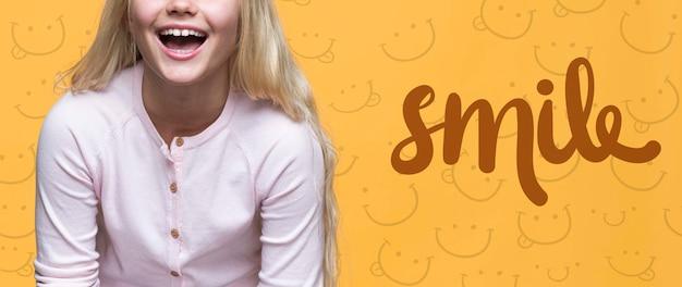 Sourire mignonne jeune fille aux cheveux blonds