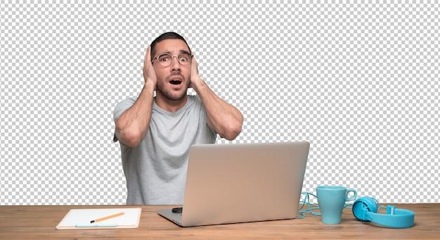 Stressé jeune homme assis à son bureau