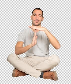 Stressé jeune homme faisant un geste de temps mort avec ses mains