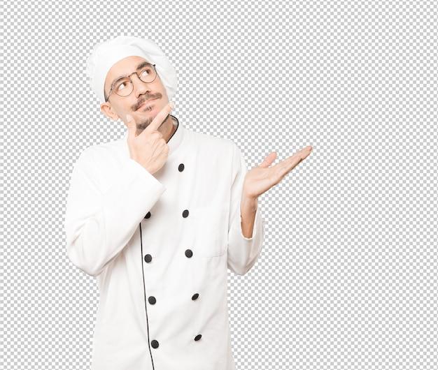 Surpris jeune chef faisant un geste de doute