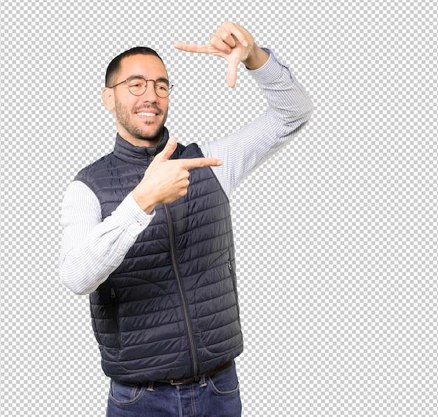 Surpris jeune homme faisant un geste de prendre une photo avec les mains