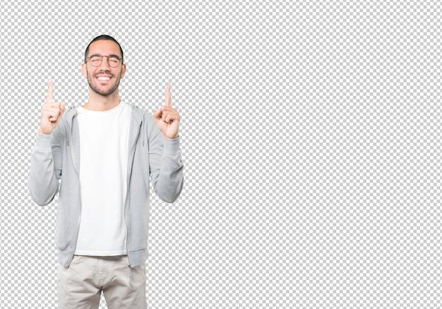 Surpris jeune homme pointant vers le haut avec son doigt