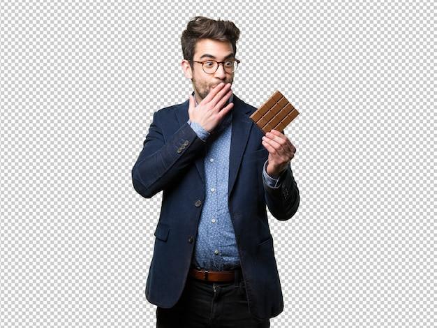 Surpris jeune homme tenant une barre de chocolat