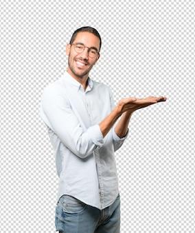 Surpris jeune homme tenant quelque chose avec sa main