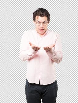 Surpris de jeune homme tenant quelque chose avec sa main