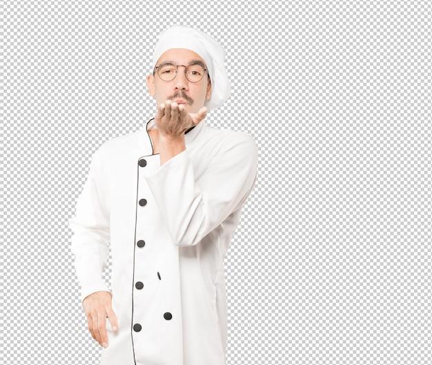 Sympathique Jeune Chef Faisant Un Geste D'envoyer Un Baiser Avec Sa Main PSD Premium