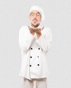 Sympathique jeune chef faisant un geste d'envoyer un baiser avec sa main