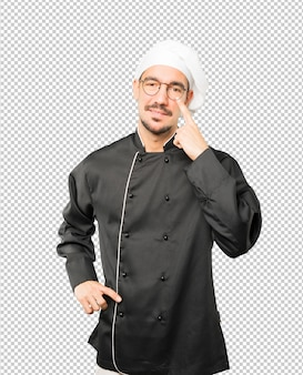 Sympathique jeune chef faisant un geste de prudence avec sa main pointée vers son œil