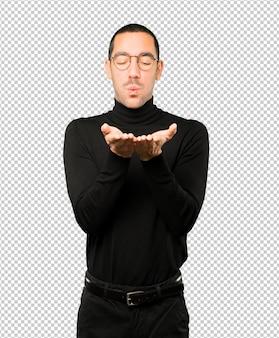 Sympathique jeune homme faisant un geste d'envoyer un baiser avec sa main