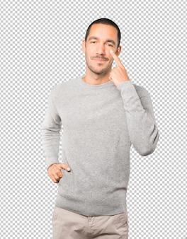 Sympathique jeune homme faisant un geste d'être prudent avec sa main pointant vers son œil