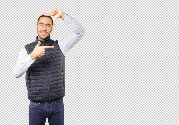 Sympathique jeune homme faisant un geste de prendre une photo avec les mains