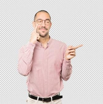 Sympathique jeune homme faisant un geste de prudence avec sa main pointant son œil