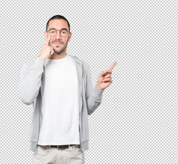 Sympathique jeune homme faisant un geste de prudence avec sa main pointant vers son œil