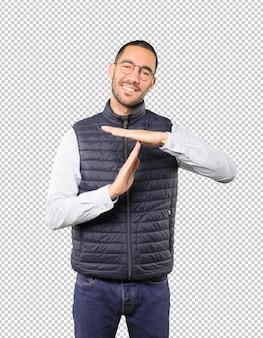 Sympathique jeune homme faisant un geste de temporisation avec ses mains