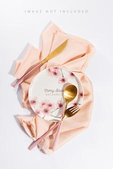 Table joliment décorée avec des assiettes blanches, des couverts aux pommes dorées sur de luxueuses nappes beiges