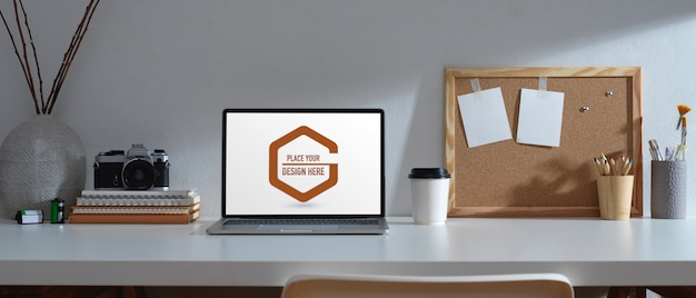 Table de travail avec maquette d'ordinateur portable, papeterie et appareil photo