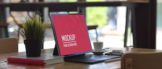 Table de travail avec maquette de tablette numérique, livre, accessoires et pot de fleurs