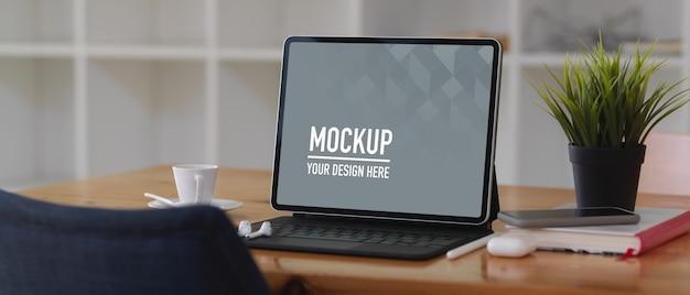 Table de travail avec maquette de tablette numérique, livre et accessoires