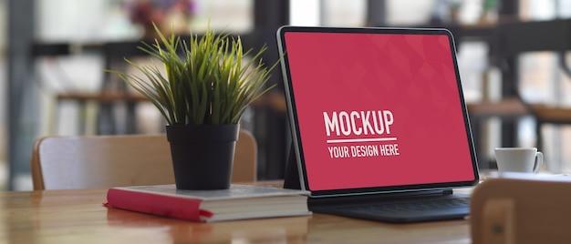 Table de travail avec maquette de tablette numérique, livre et pot de fleurs