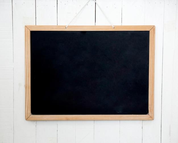 Tableau noir vide sur mur en bois