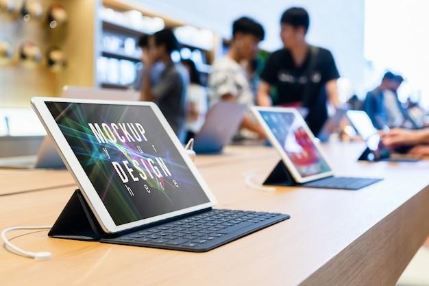 Tablette écran vert vierge maquette dans le magasin informatique