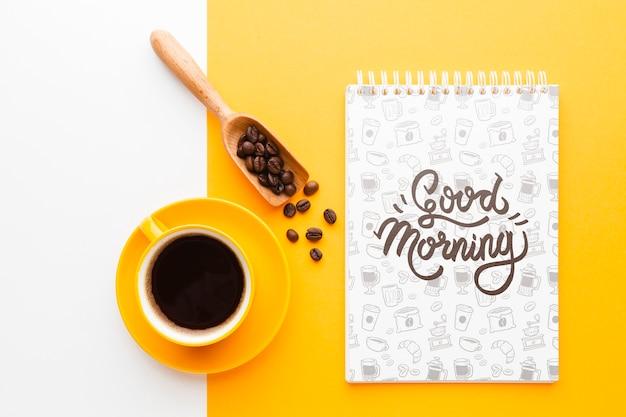 Tasse à café à côté d'une maquette de cahier