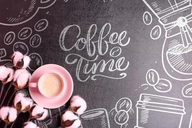 Tasse en céramique rose avec boisson au café frais et fleurs de coton naturel sur fond de cuir noir maquette, espace copie.