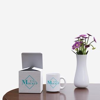 Tasse de maquette simple avec boîte de combinaison avec des fleurs