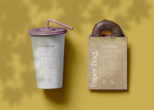 Tasse en papier avec sac et maquette de beignet
