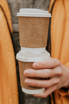 Tasses à café recyclées maquette psd avec gros plan à la main