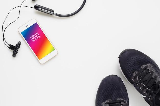 Téléphone portable avec écouteurs bluetooth et chaussures de course sur fond blanc