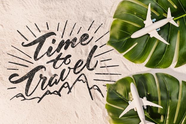 Temps de voyager, lettrage avec des feuilles de palmier et des avions jouets