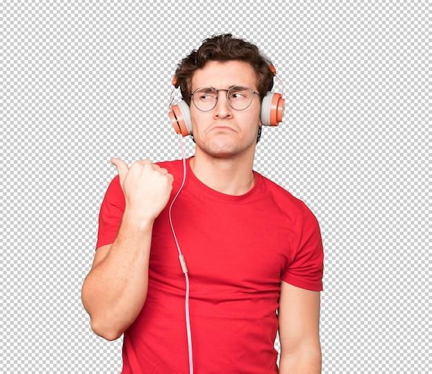 Triste jeune homme à l'aide d'écouteurs