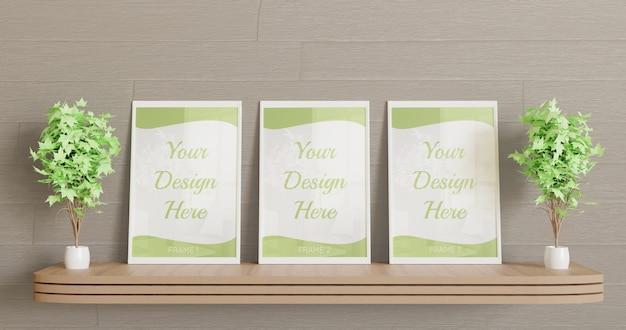 Trois maquettes de cadre blanc debout sur le bureau mural en bois avec des plantes de décoration