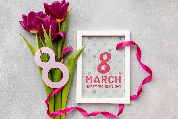 Tulipes à côté de la date de la journée des femmes sur la table
