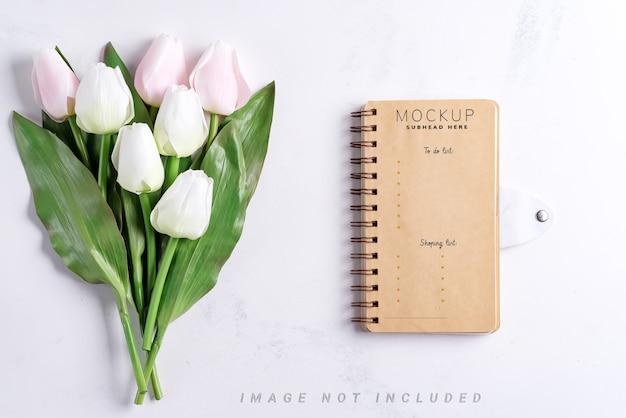 Tulipes pastel avec maquette de cahier sur fond de marbre blanc