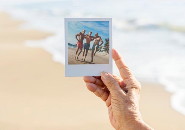 Vieille dame tenant une photo à la plage