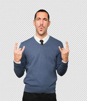 Vilain jeune homme faisant un geste rock