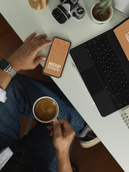 Vue aérienne d'un homme prendre une pause avec le smartphone, y compris un tracé de détourage et une tasse de café