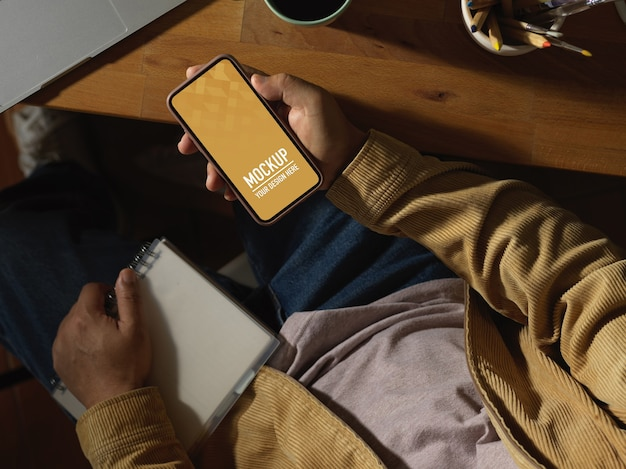 Vue aérienne de la main masculine tenant la maquette du smartphone