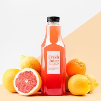 Vue avant de la bouteille de jus en verre avec pamplemousse et citrons