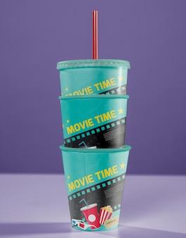 Vue avant des tasses de cinéma empilées avec de la paille