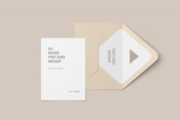 Vue de dessus d'une carte postale verticale et d'une maquette d'enveloppe
