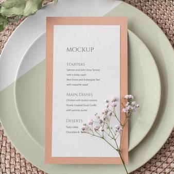 Vue de dessus de la disposition de la table avec assiettes et maquette de menu de printemps