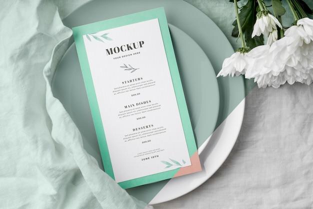 Vue de dessus de la disposition de la table avec des fleurs de printemps et une maquette de menu