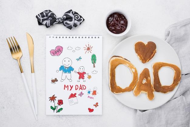 Vue de dessus du bloc-notes avec assiette de crêpes et muffins pour la fête des pères